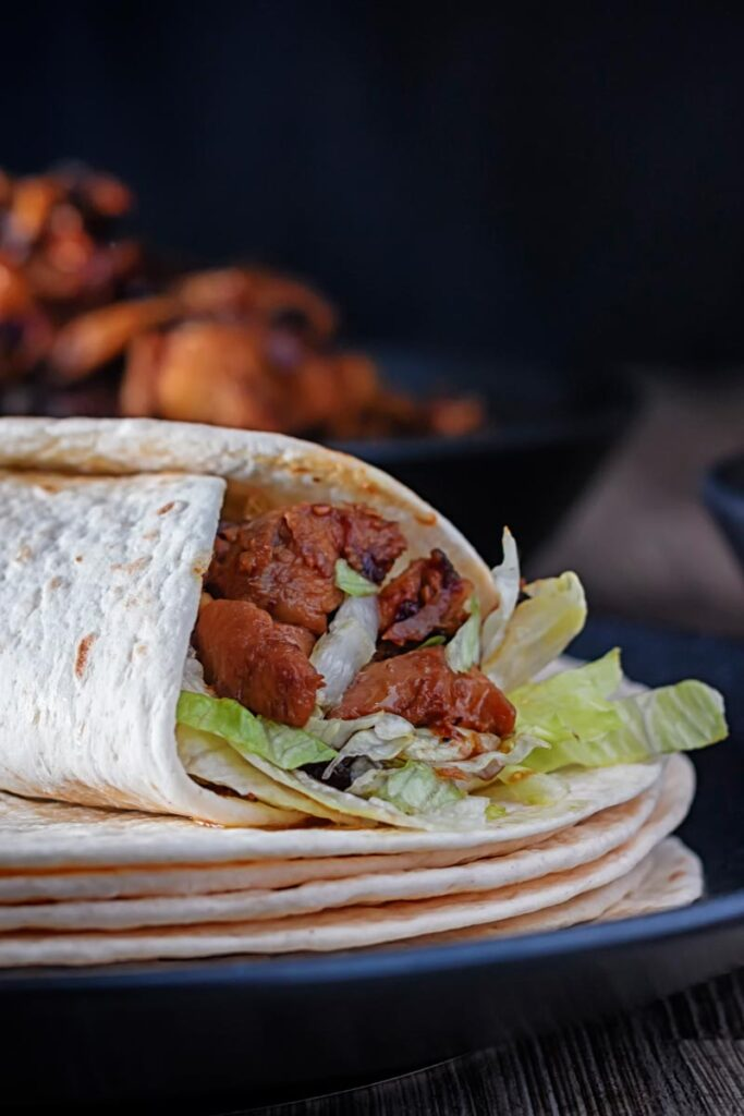 An achari chicken wrap using flour tortilla