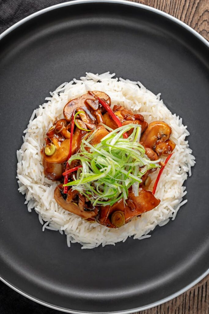 Portrait overhead image of a Chinese chicken and mushroom stir fry served ona black plate with shredded spring onion and white rice