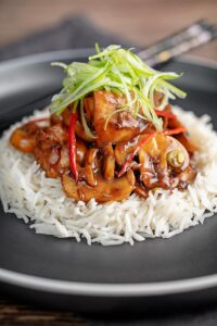 Portrait image of a Chinese chicken and mushroom stir fry served ona black plate with shredded spring onion and white rice