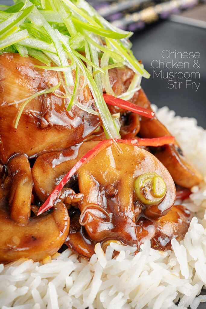 Portrait close up image of a Chinese chicken and mushroom stir fry served with shredded spring onion and white rice with text overlay