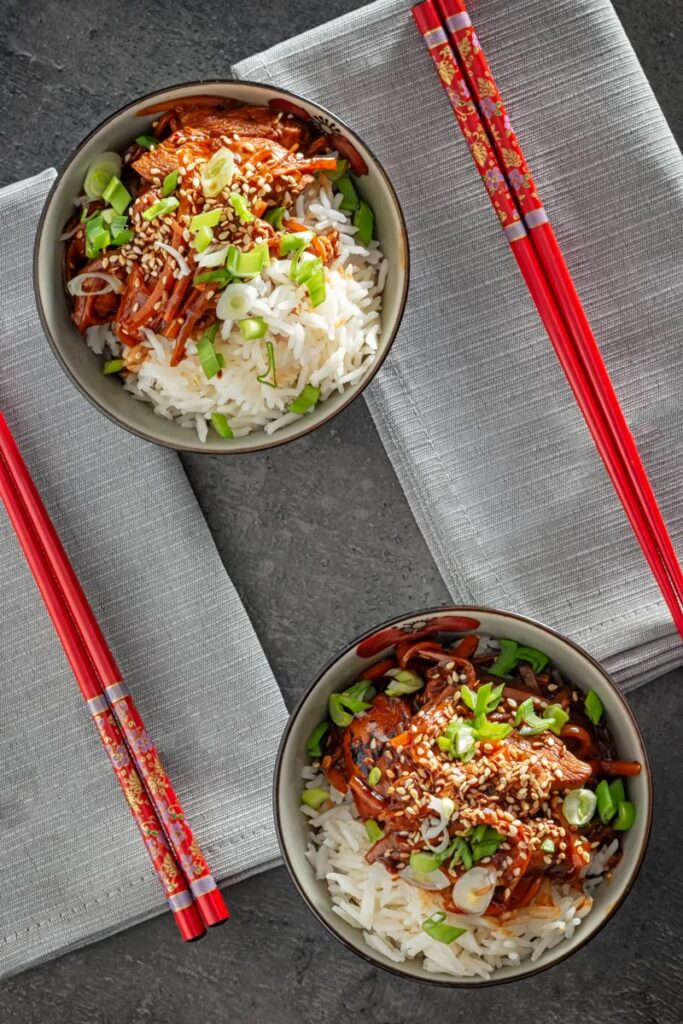 Overhead portrait image of two bowls of chinese orange chicken stir fry served with white rice sprinkled with sesame seeds