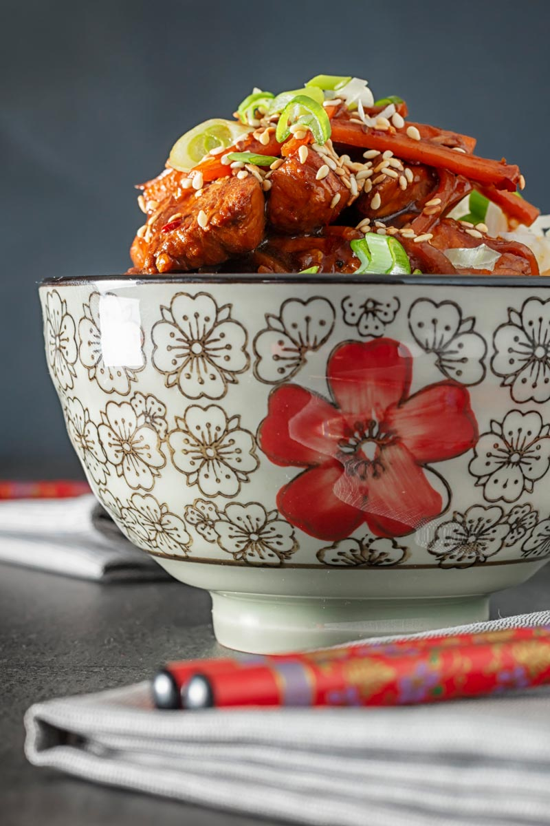 Portrait image of a Chinese orange chicken stir fry garnished with sesame seeds and spring onions