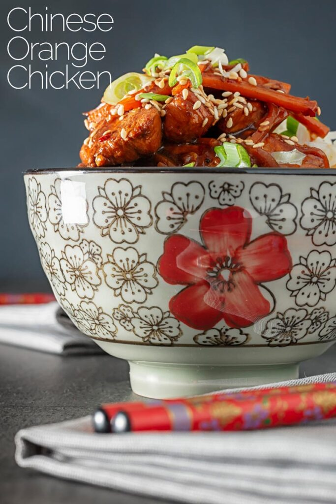 Portrait image of a Chinese orange chicken stir fry garnished with sesame seeds and spring onions with text overlay