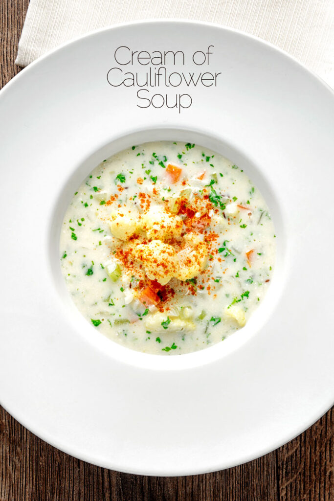 Portrait overhead image of cauliflower florets ina cream of cauliflower soup with flecks of parsley and paprika with text overlay
