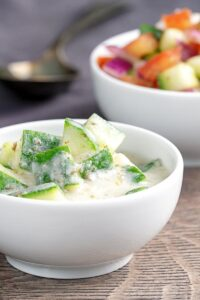Portrait image of a cucumber and mint raita served in a small white bowl.