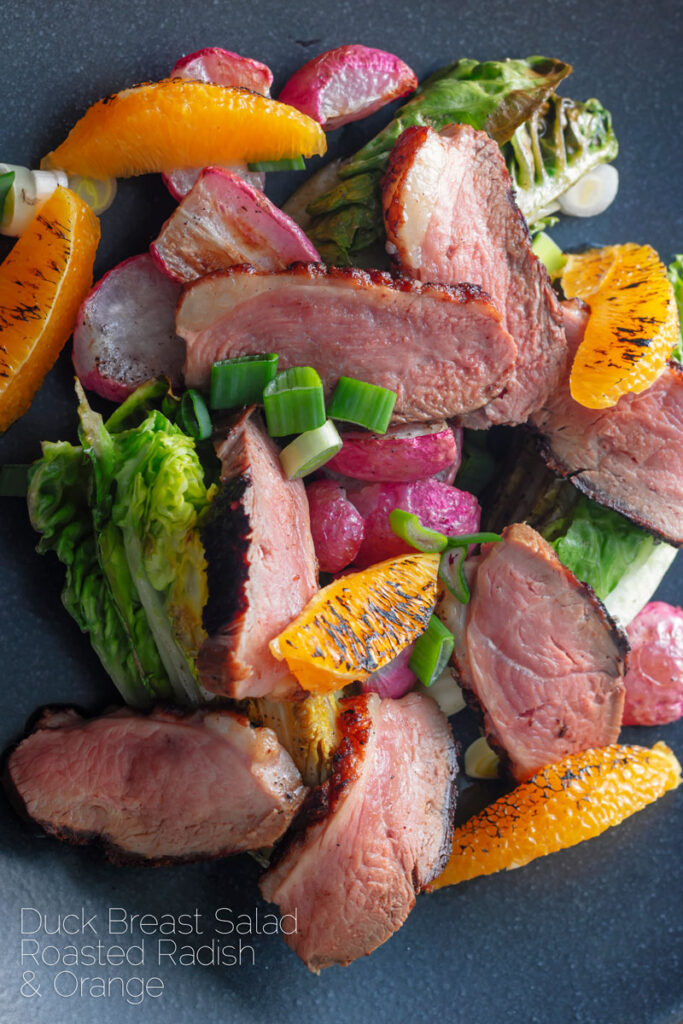 Portrait overhead image of a sliced duck breast salad featuring seared orange and roasted radishes served on a black plate with text overlay