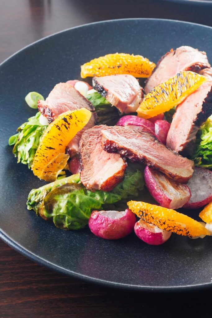 Portrait image of a sliced duck breast salad featuring seared orange and roasted radishes served on a black plate