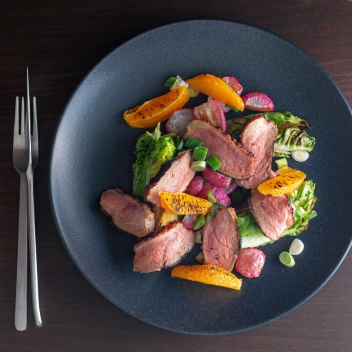 Square overhead image of a sliced duck breast salad featuring seared orange and roasted radishes served on a black plate
