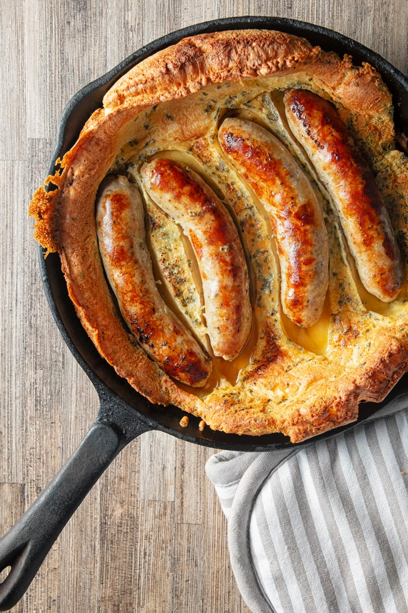 Portrait overhead image of toad in the hole, or sausages cooked in a Yorkshire pudding batter cooked and served in a cast iron skillet