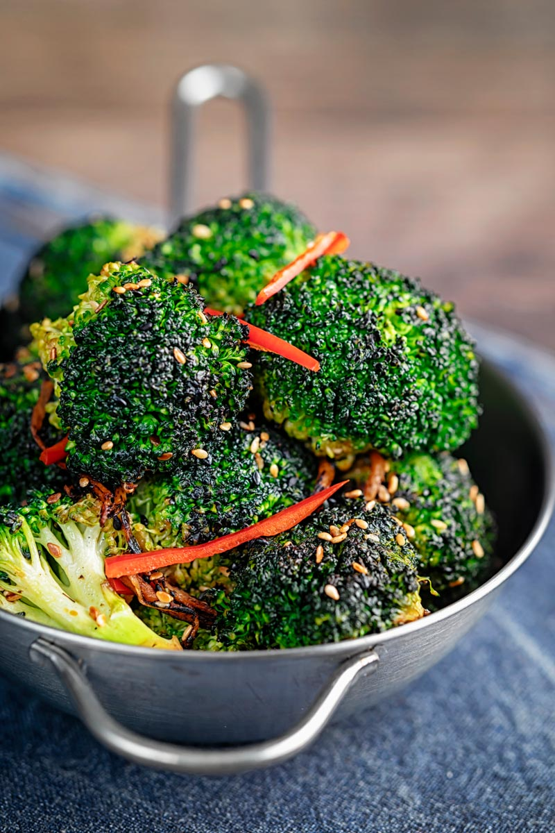 Portrait image of stir fry broccoli featuring sesame seeds, ginger and red pepper served in a mini wok