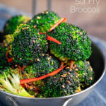 Portrait image of stir fry broccoli featuring sesame seeds, ginger and red pepper served in a mini wok with text overlay