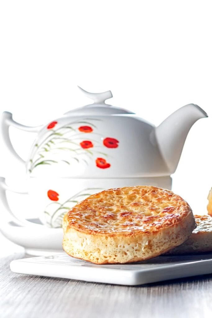Portrait image of a toasted homemade English crumpet on a white plate in front of a teapot