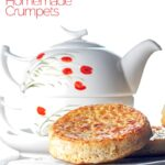 Portrait image of a toasted homemade English crumpet on a white plate in front of a teapot with text overlay