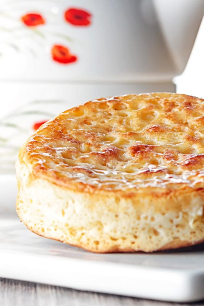 Portrait close up image of a toasted homemade English crumpet on a white plate in front of a teapot