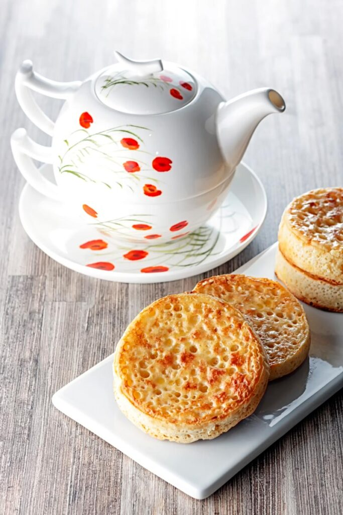 Portrait image of buttered crumpets served on a rectangular white plate with a pot of tea!