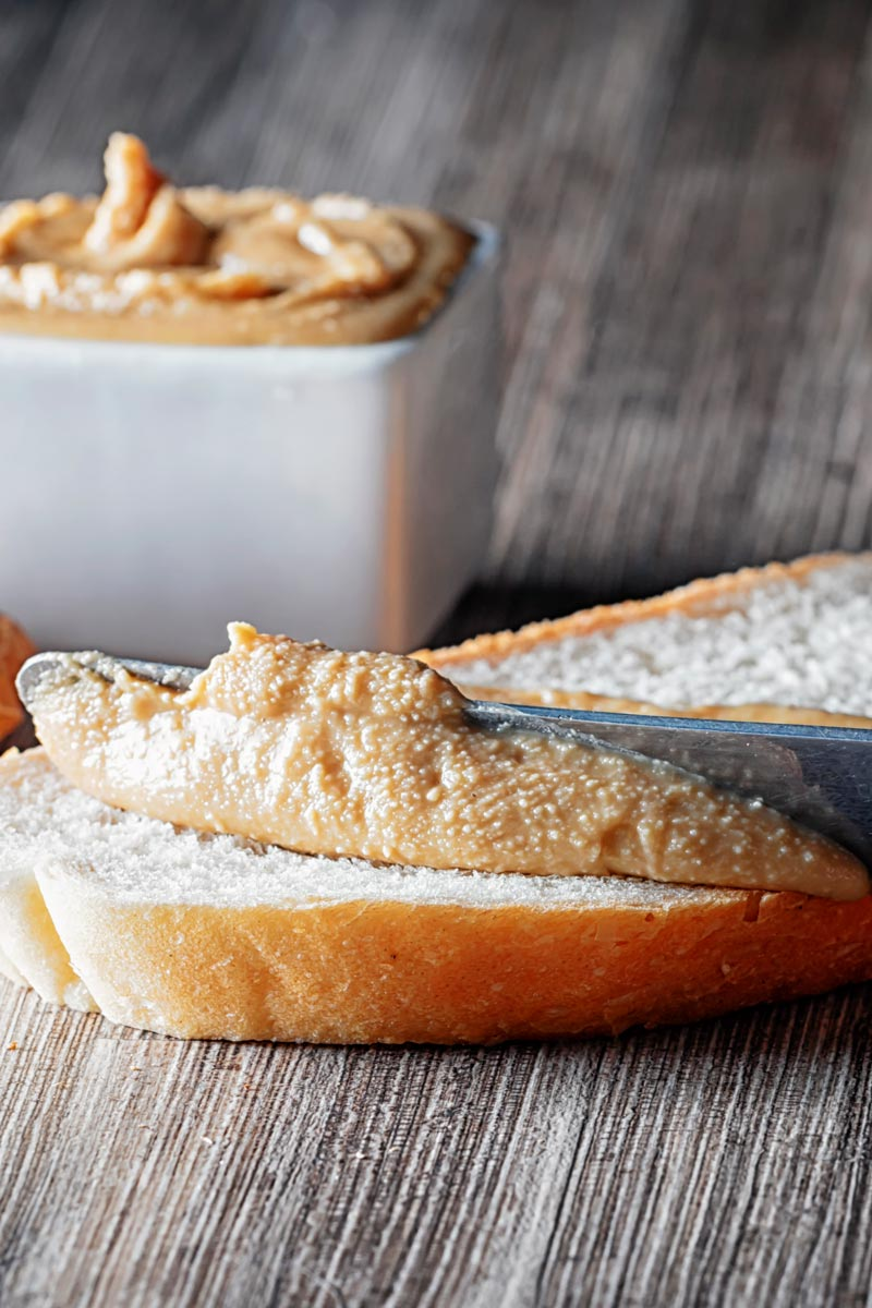 Portrait image of homemade peanut butter being spread on white bread with unshelled peanuts and a bowl of peanut butter in the background