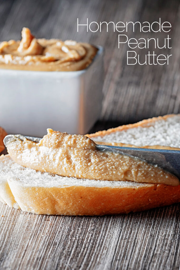 Portrait image of homemade peanut butter being spread on white bread with unshelled peanuts and a bowl of peanut butter in the background with text overlay