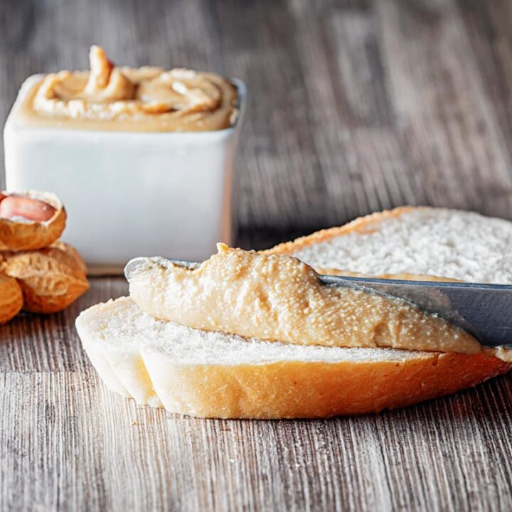 Square image of homemade peanut butter being spread on white bread with unshelled peanuts and a bowl of peanut butter in the background