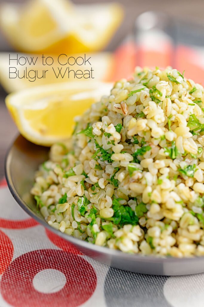 Portrait image of perfectly cooked bulgur wheat with fresh parsley and lemon wedges with text overlay