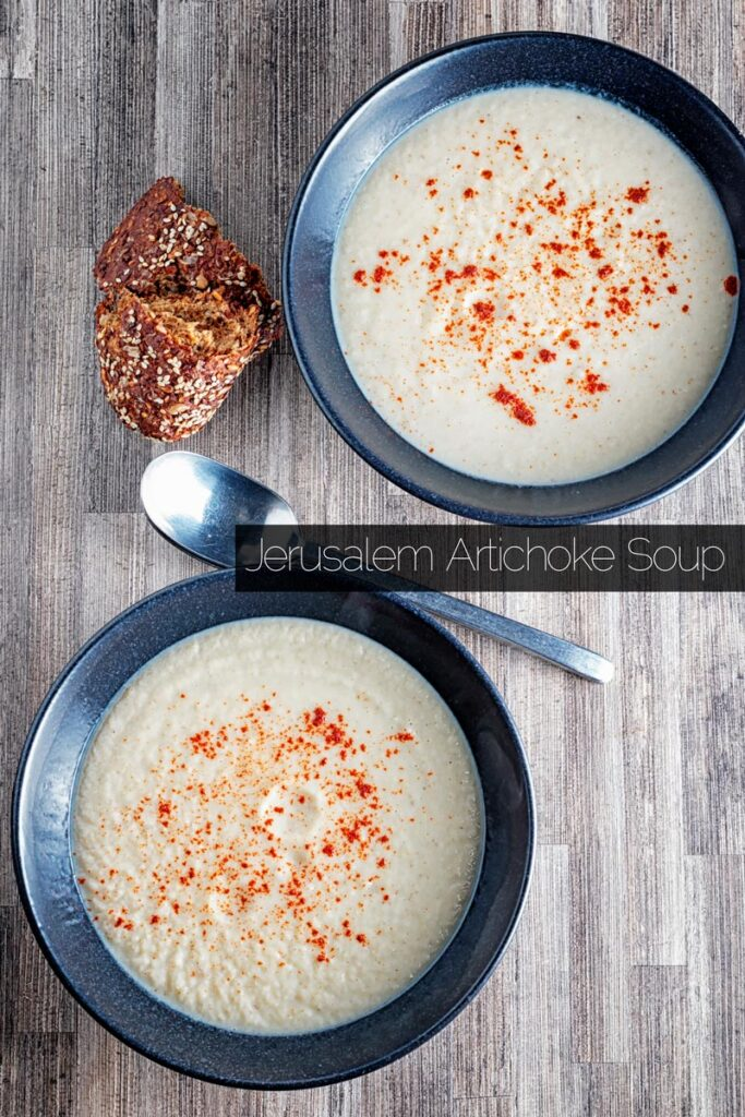 Portrait overhead image of Jerusalem artichoke soup served in a black bowls with a sprinkle of paprika with text overlay
