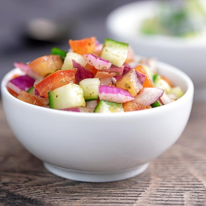 Square image of an Indian kachumber side salad served in a white bowl