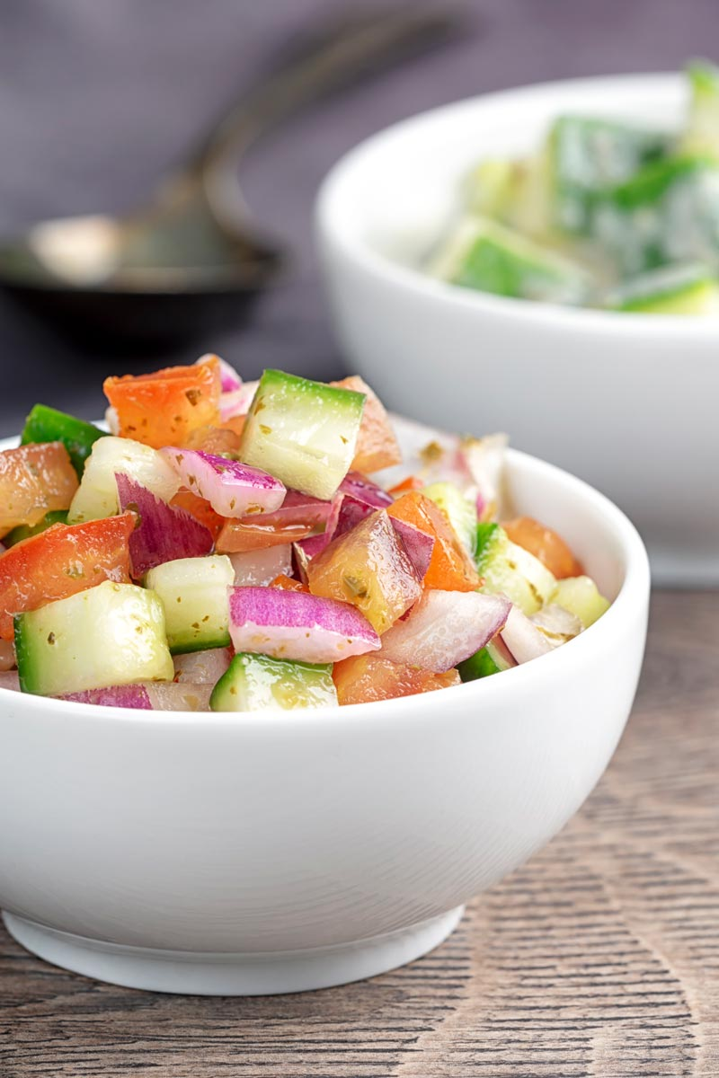 Portrait image of an Indian kachumber side salad served in a white bowl