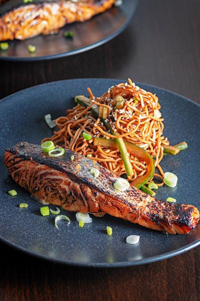 Portrait image of grilled korean salmon fillet with stir fried noodles served on a black plate