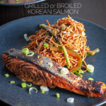 Portrait image of grilled korean salmon fillet with stir fried noodles served on a black plate with text overlay