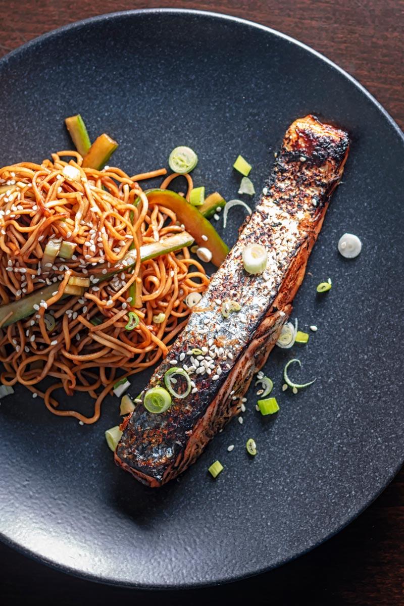 Portrait overhead image of grilled Korean salmon fillet served on a black plate with stir fried noodles
