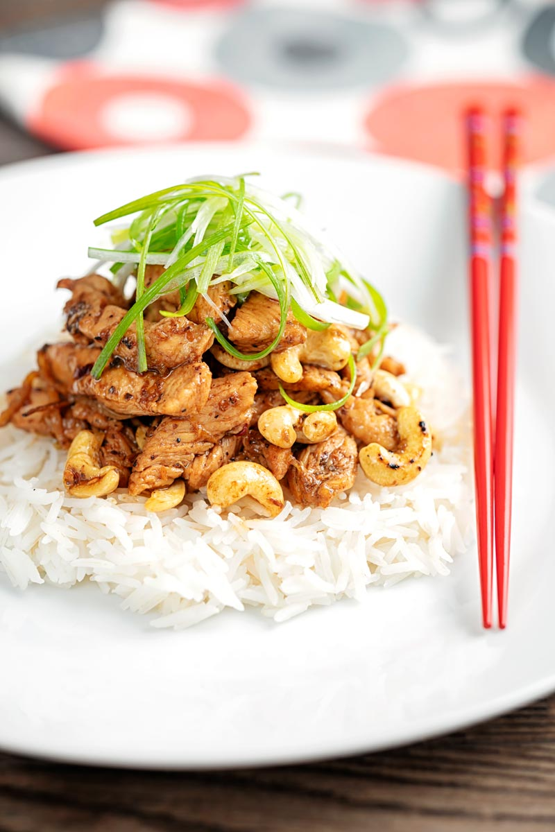 Portrait image of kung pao chicken served with rice and shredded spring onions on a white pate with red chopsticks