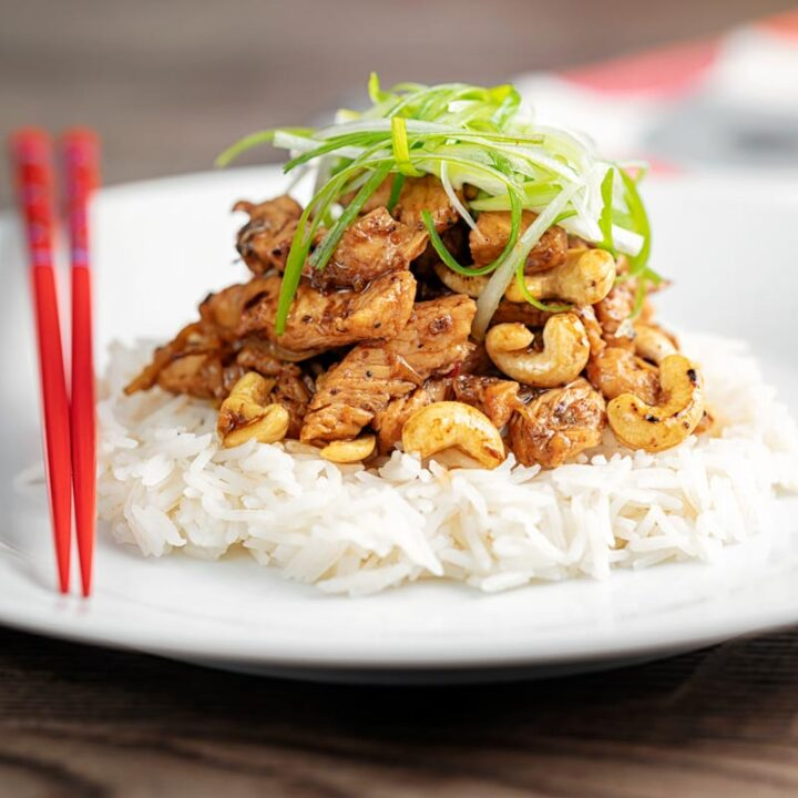 Square image of kung pao chicken served with rice and shredded spring onions on a white pate with red chopsticks