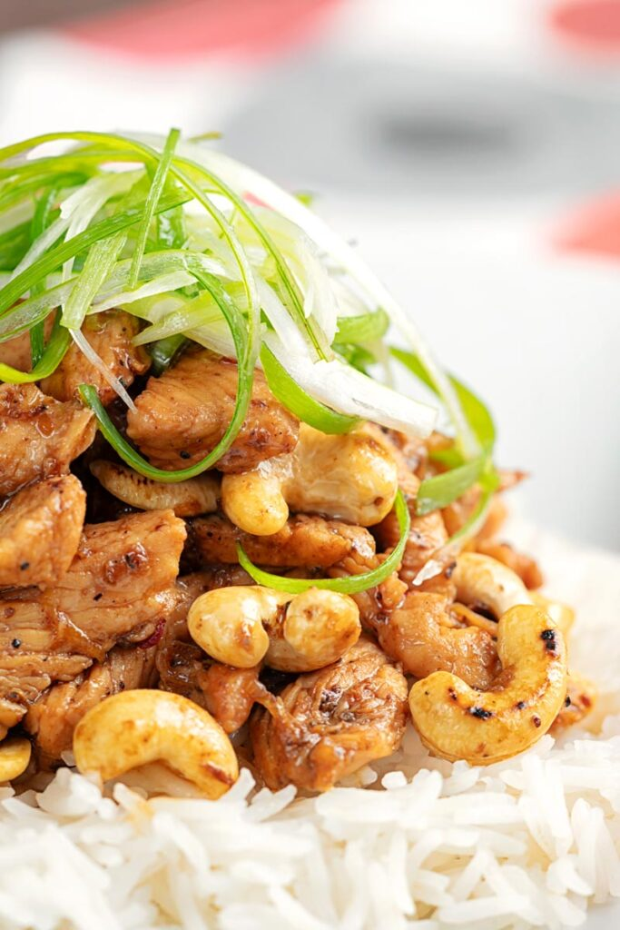 Portrait close up image of kung pao chicken served with rice and shredded spring onions on a white plate