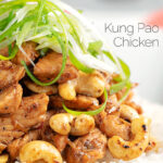 Portrait close up image of kung pao chicken served with rice and shredded spring onions with text overlay
