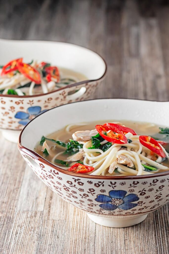Portrait image of chicken noodle soup made with leftover chicken served in an Asian style bowls decorated with a blue flower