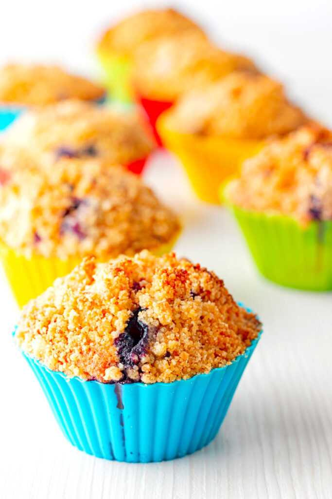 Portrait image of lemon and blueberry muffins in colourful silicon muffin cases on a white backdrop
