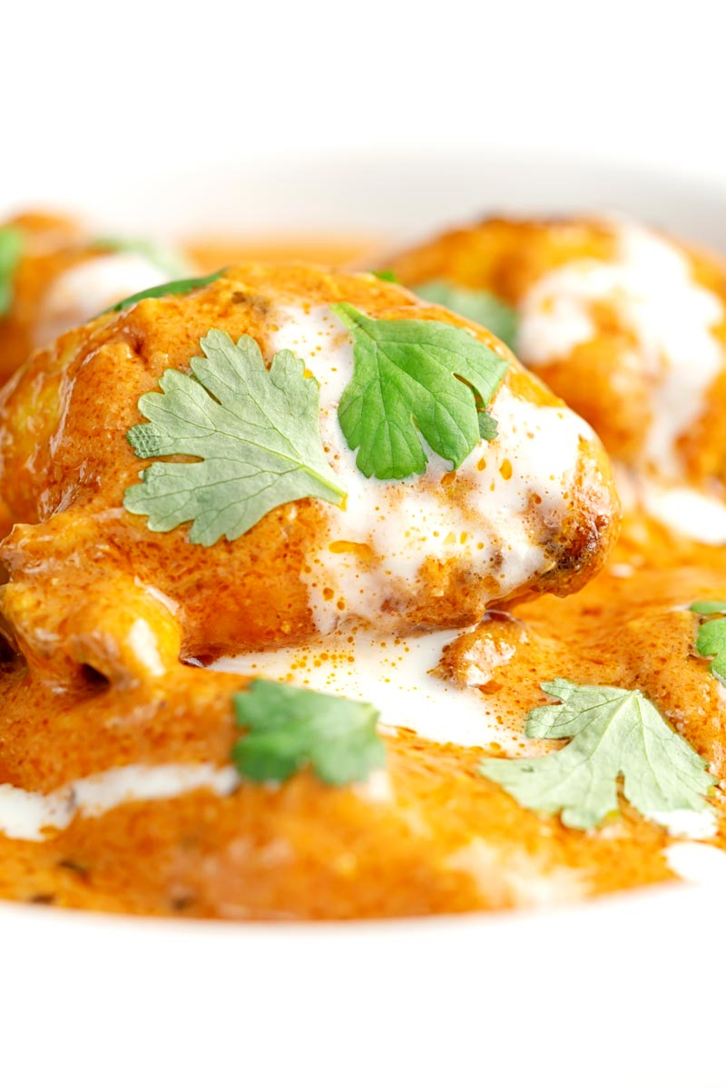 Portrait close up image of murgh makhani or a butter chicken curry with a swirl of cream and fresh coriander