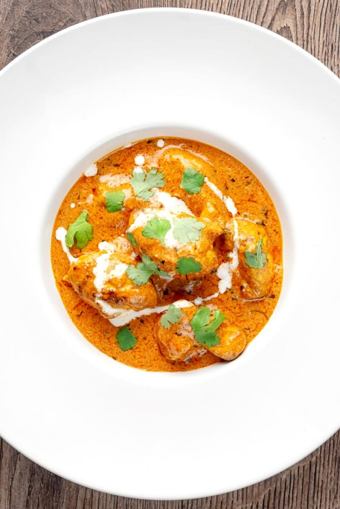 Portrait overhead image of murgh makhani or a butter chicken curry with a swirl of cream and fresh coriander served in a white bowl