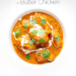 Portrait overhead image of murgh makhani or a butter chicken curry with a swirl of cream and fresh coriander served in a white bowl with text overlay