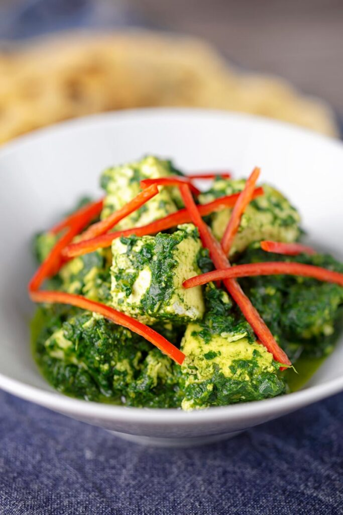 """Portrait image of a classic Indian Palak Paneer spinach and """"cottage"""" cheese curry"""