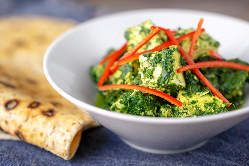 """Landscape image of a classic Indian Palak Paneer spinach and """"cottage"""" cheese curry"""
