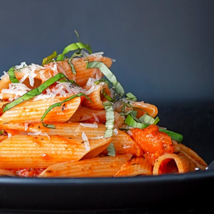 Square image of penne arrabiata served on a black plate with a garnish of basil and Parmesan cheese