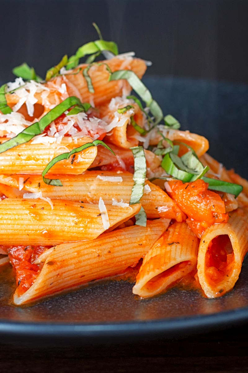 Porttrait image of penne arrabiata served on a black plate with a garnish of basil and Parmesan cheese