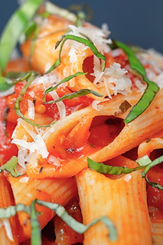 Portrait close up image of penne arrabiata with a garnish of basil and Parmesan cheese