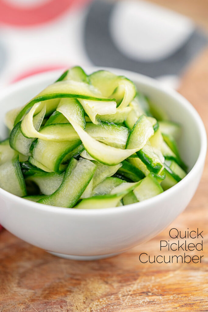 Portrait image of quick pickled cucumber ribbons served in a white bowl with text overlay