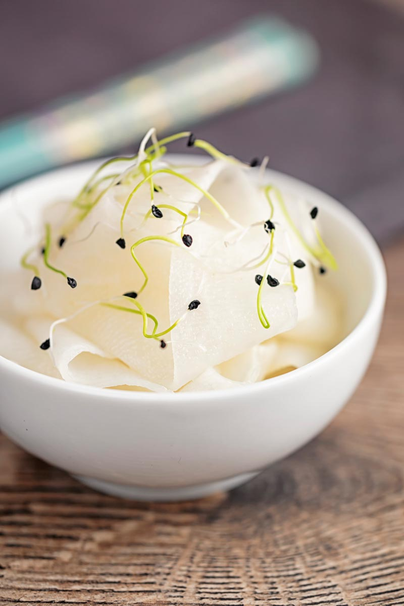 Portrait image of ribbons of pickled daikon served in a small white bowl with sprouted onion seeds