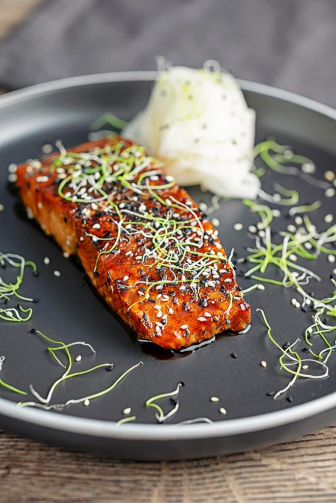 Portrait image of a glazed salmon teriyaki topped with sesame seeds and garnished with sprouted onion seeds served with pickled daikon