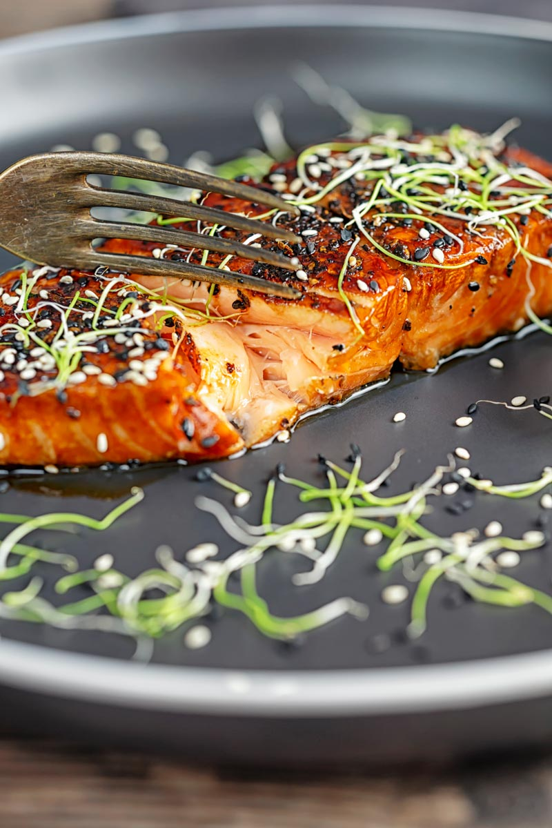 Portrait image of a glazed salmon teriyaki showing internal texture. Topped with sesame seeds and garnished with sprouted onion seeds