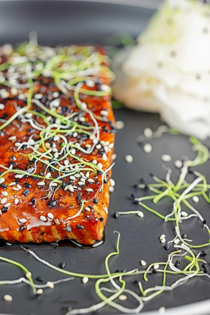 Portrait close up image of a glazed salmon teriyaki topped with sesame seeds and garnished with sprouted onion seeds served with pickled daikon