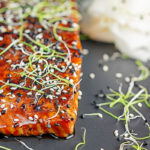 Portrait close up image of a glazed salmon teriyaki topped with sesame seeds and garnished with sprouted onion seeds served with pickled daikon with tect overlay