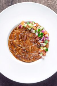Portrait overhead image of a rajma masala kidney bean curry served with a kachumber salad in a white bowl